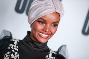 Black woman wearing soft velvet pink head wrap and black mock neck top with floral design.