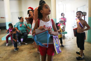 Children in brightly colorled clothes in shelter in Puerto Rico, child in front wears red and white and carries blue bag