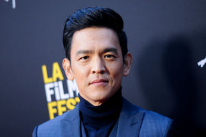 John Cho. An Asian man with hair combed back stands in front of a black Background