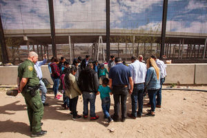 Migrants from Honduras, Guatemala and El Salvador stand in a prayer circle underneath the Paso Del Norte Bridge as an immigration official in a green uniform watches over them.