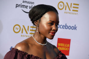 A Black woman side view on the red carpet with her hair up and wearing a shoulder-bearing burgundy dress.