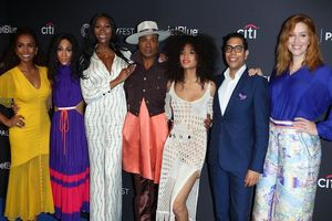 Seven people of color stand side by side at a glamorous event.