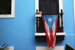A Puerto Rican flag hangs from a black-shuttered window set in a bright blue exterior wall
