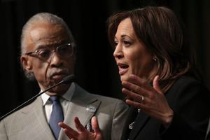 A Black man on the left with a Black woman at a podium next to him with a black background.