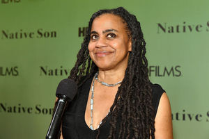 """A Black Woman with long hair and black shirt stands at event in front of wall that reads """"Native Son'."""""""