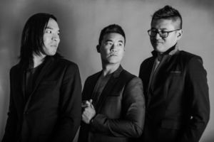 """(L to R) Ken Shima, Joe X. Jiang, Simon """"Young"""" Tam. Black and white photograph of three Asian men side by side in suits."""