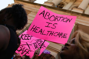 Black woman standing in front of signs supporting abortion rights