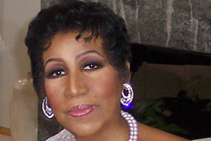 Aretha Franklin. Black woman with pixie cut and two-strand pearls.