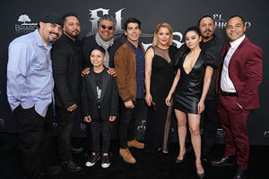 "Cast of ""Le Chicano."" Nine people stand in a line in front of black backdrop"
