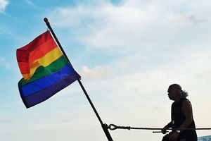 GLAAD. Shadowy figure of man waving pride flag on a boat.