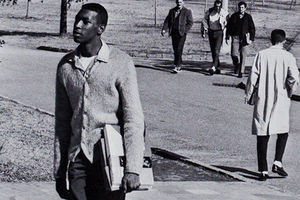 Joseph Vaughn. Black student wears a cardiagan and stands outside with books in hand in black and white photo.