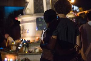 back of a Black couple facing an altar in Dallas at nighttime vigil