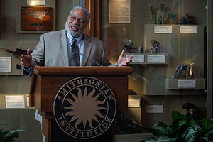 Lonnie G. Bunch III. Older Black man in gray suit, tie, glasses, stands in front of Smithsonian podium.