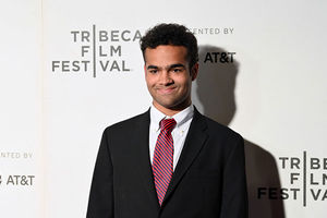 Young Black man. Curly hair black suit jacket, white shirt, and red tie.
