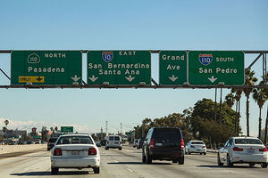 Rideshare strike. Interstate signs for 110 North (Pasadena) - 10 East (San Bernardino, Santa Ana), Grand Avenue, and 110 South (San Pedro).