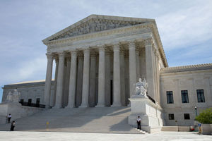 Supreme Court. White building with multiple white pillars and multiple steps. Guards stand on stairs.