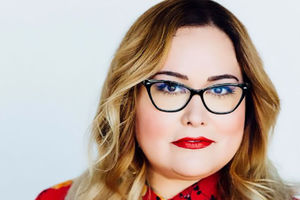 Tanya Saracho. Latinx woman with blonde shoulder length hair, blue glasses and red floral top.