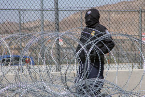 Immigration agent wears all black and covers his face with a black scarf as he stands near a barbed wire fence.