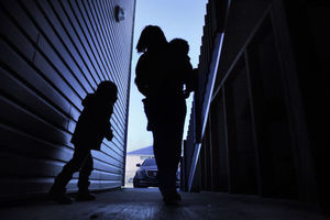 Silhouette of a woman carrying a toddler with a child who appears between five and six years old walking to her left they are all facing an opening that peers at a car on a driveway