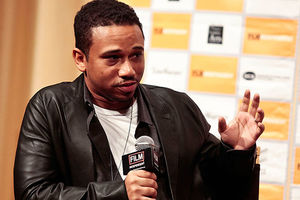 Aaron McGruder. Black man with short dark hair wearing black jacket, white T, holding a microphone.
