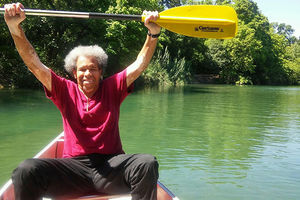 Albert Woodson. Older Black man with gray Afro holding up oar while in a canoe.