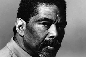 Alvin Ailey. Black and white closeup of Black man in profile with short black hair and facial hair.