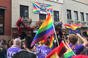 Stonewall Inn. A sea of rainbow Pride flags and marchers in front of Stonewall Inn.