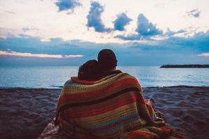 the back of a couple laying on the beach with a multicolored quilt covering them