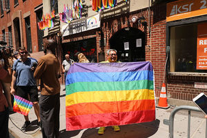 Stonewall Inn. Middle aged person stands outside the bar holding a large rainbow flag.