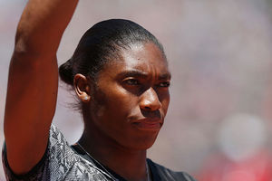Caster Semenya. Black woman in gray top with dark hair pulled back into a low bun.