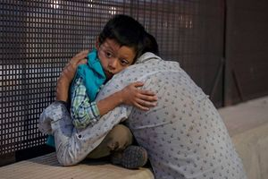 A young boy with brown hair wears an emotional expression as he sits on a a concrete platform and hugs his father.