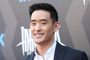 Mike Moh. Korean American man with short dark hair wearing a dark suit jacket and white shirt in front on a step and repeat.