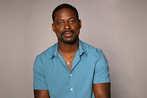 Sterling K. Brown. Black man wearing glasses and blue polo shirt.