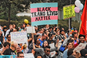 a rally with someone holding a sign that reads Black Trans Lives Matter
