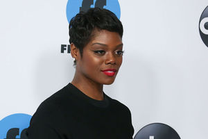 Afton Williamson: Black woman with dark pixie haircut, wearing a black top.