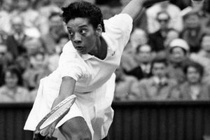 Althea Gibson. Black and white photo of Black woman dressed in white playing tennis.