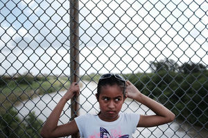 Young girl with dark hair and a pink butterfly on her white t-shirt stands in front of a chainlink fence.