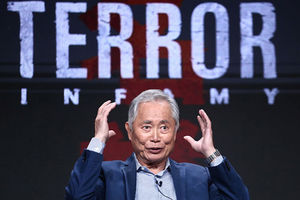 "George Takei. Elder Japanese-American man with short gray hair wearing blue suite jacket and striped shirt seated in front of sign reading ""Terror."""
