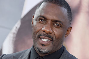 Idris Elba. Black man with short dark hair wearing dark gray jacket, black shirt and black tie.