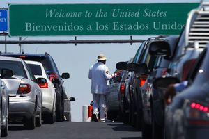 Long line of cars wait on a road under a large sign above that reads, Welcome to the United States.