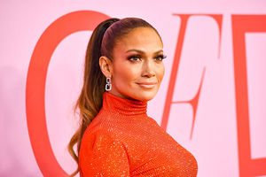 Jennifer Lopez. Latinx woman with blond hair in a high ponytail, wearing red high neck top standing in front of step and repeat.