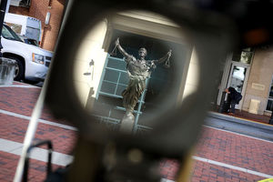 Dark green statue of Justice magnified through black camera lens on red brick and brown stone walkway in front of brown building and white car