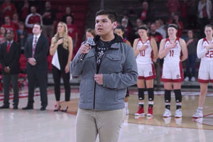 Steven Wilson. Young Lakota man with short dark hair wearing gray jacket and tan pants performing National Anthem in University of South Dakota's gym.