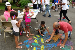 Night Out for Safety and Liberation. Two Black adults and three Black children create street art with chalk.