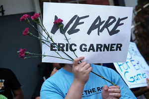 "Eric Garner protest. Person holds pink flowers and white sign that reads, ""We are Eric Garner."""