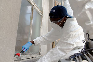 """Touching History."" Black person dressed in white protective gear works on the floor restoring a window."