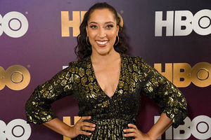 Robin Thede. Black woman wearing black and gold V-neck dress with high ponytail standing in front of HBO step and repeat.