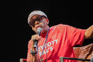 Spike Lee. Middle aged Black man wearing red t-shirt, blue glasses and white baseball cap.
