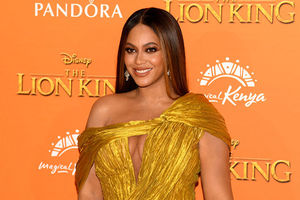 Beyoncé. Black woman with long straight blond hair wearing gold dress in front of an orange step and repeat.