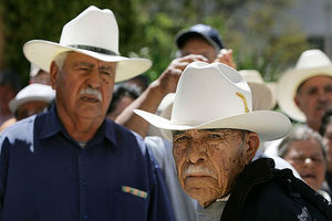 Braceros. Older Latinx men wearing workers hats and dark-colored tops.